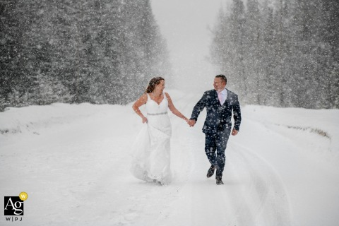 Natural Bridge, Field, BC, Canada creative couple wedding portrait of the Bride and groom having fun during the snowfall