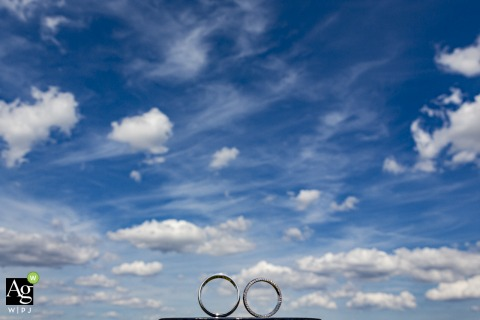 Tuscany wedding detail picture of the rings against a big blue sky with clouds