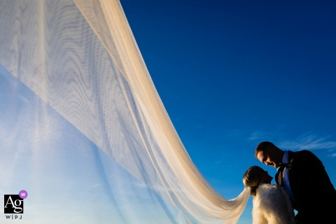Lake Tahoe, Neveda creative wedding day portrait of the Bride and Groom at Lake under bluebird sky