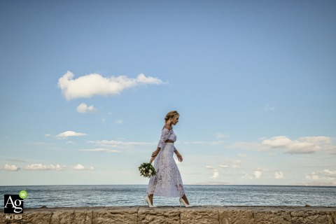 Toscaanse bruid die voor de sessie van het huwelijksportret op een muur bij het strand loopt