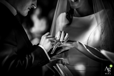 Creative wedding detail image fromLombardy of the groom placing thte ring on the bride