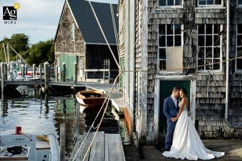 Osterville, MA creative New England wedding portrait of the Bride and groom by the harbor water and fishing village