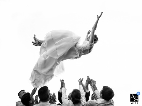 Strasbourg, Bas-Rhin adventurous wedding portrait of the bride being tossed into the air by the men