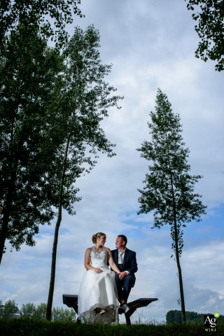 De Klinge bride and groom wedding portrait session on a bench with trees
