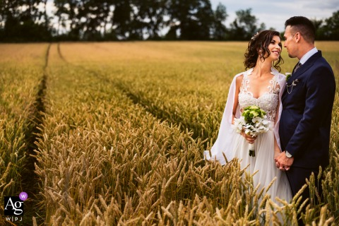 Banovci, Slovenia creative open field wedding portrait of the Groom and bride standing on the wheat field