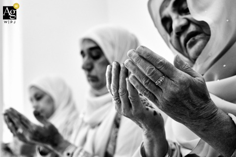 Black and white wedding photography from a Private venue in Birmingham, UK of Family of the bride praying