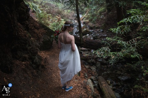 Artistic wedding photo from a Redwood grove near Mt. Tam in Marin County, California as the bride was walking through a stretch of forest on the way to the ceremony site, a pause for a quick portrait