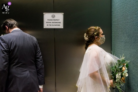 Wedding image from the 2nd District Court of Appeals, Fort Worth, TX showing the bride and groom standing apart from each other in an elevator under a social distancing covid sign