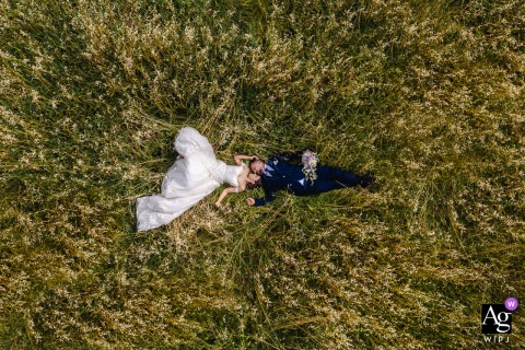 Monferrato Resort, Italy wedding couple artistic image session of the bride and groom lying on the grass