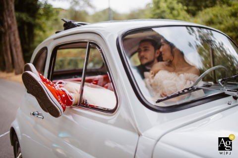 Sovicille Town Hall, La Sosta del Cavaliere, Rosia wedding couple artistic image session  of the bride and groom are embraced inside an old 500 with legs stretched out, the legs of the bride come out of the car and fire is right on the red converse