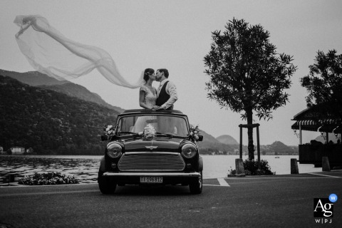 Church of Saints Cyricus and Julitta wedding couple artistic session of the the bride and groom get out of the roof of an old mini, are located on the edge of the lake of morcote, the sail of the bride is pushed up by the veil and stretches in the air