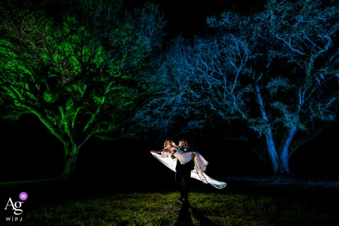 Addison Woods Wedding & Event Venue, Spring, TX wedding couple artistic image session of the groom carrying bride under oak trees at night