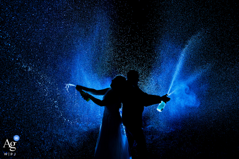 Rocky Mountain National Park, Estes Park, CO wedding couple artistic image session of the bride and groom spraying champagne at night