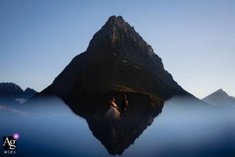 Sessione di immagine artistica degli sposi del Glacier National Park la montagna riflessa con la coppia