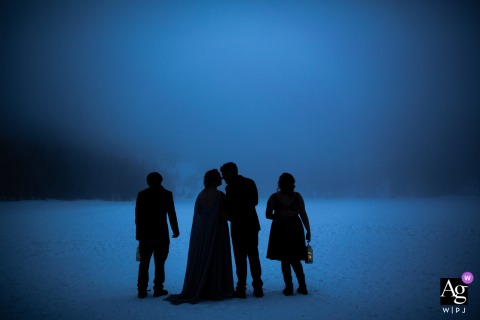 Bear Lake, Rocky Mountain National Park, Colorado wedding party artistic image session with the wedding couple and their children taking in the blue twilight on the frozen lake where they got married.