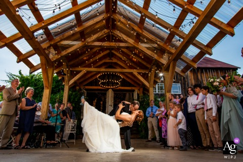 The Adirondacks, New York wedding venue reception photography showing final dip at the end of the first dance in the outdoor pavilion surrounded by all their family and friends