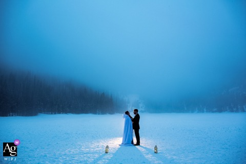Bear Lake, Rocky Mountain National Park, Colorado wedding couple artistic image session with lanterns surrounding the bride and groom on their foggy and snowy wedding day