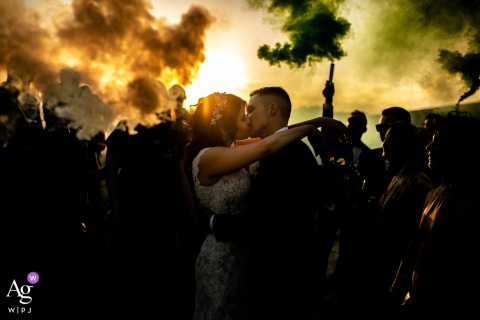 Tenuta Carretta, Italy wedding couple artistic image session - a portrait of the couple kissing at the sunset with smoke bombs