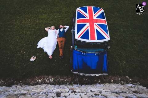 Hauts-de-France wedding couple artistic image session of the bride and groom lying next to their british mini cooper