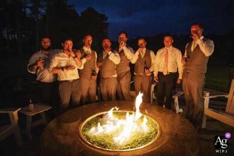 Pinehills, Plymouth, Massachusetts wedding party immagine artistica sessione dei ragazzi fumare sigari intorno firepit al crepuscolo