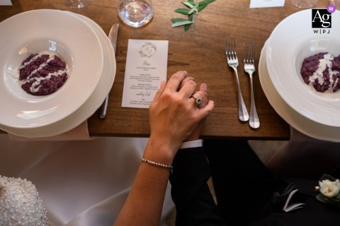 Tuscany artful style wedding detail of the food and hands of the couple