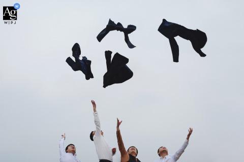 Séance d'image artistique de la fête de mariage du Fujian du marié et des garçons d'honneur jetant leurs manteaux en l'air