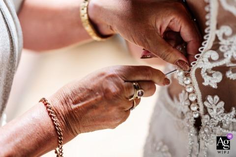 Pumping House, Nottinghamshire, Royaume-Uni mariage de style artistique détail photo de la mariée a aidé dans sa robe de mariée par sa mère
