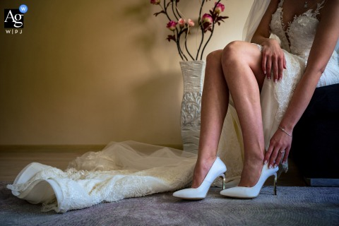 Gotse Delchev, Bulgaria artful style wedding detail picture of the bride putting her shoes on