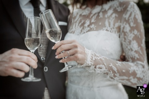 KFarm Vicenza artful style wedding detail picture of Detail of the newlyweds hands holding glasses for a toast