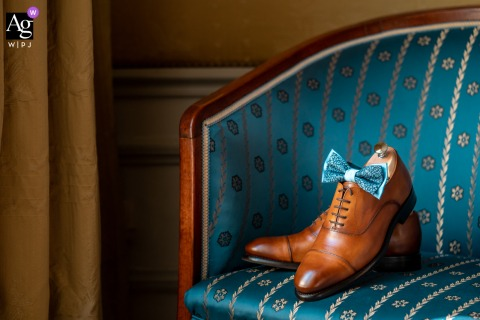 Paris artful style wedding detail picture of the Groom shoes on a chair with a bow tie