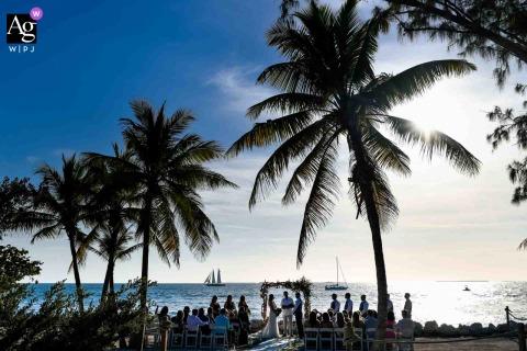 Photographie de cérémonie en plein air sur le lieu de mariage de Key West, en Floride, montrant tous les éléments qui ont amené le couple en Floride - plage, palmiers, eau, bateaux