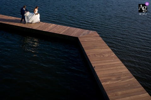Netherlands wedding venue outdoor reception photography of the bride and groom walking back to the shore via this jetty After a small photo opportunity, this is a drone photo