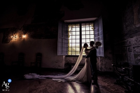 Castello di Fosdinovo Massa wedding couple artistic image session indoors against a full pane of windows