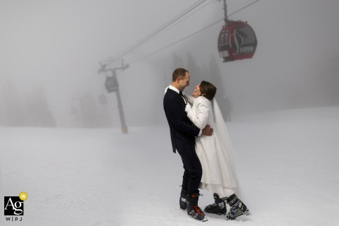 Aspen wedding couple artistic image session in the winter snow showing The bride and groom share a laugh while posing for a portrait as the fog rolls in on Aspen mountain following their micro wedding ceremony