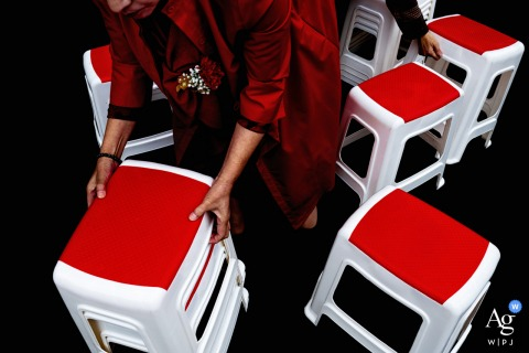 Sichuan artful style wedding detail picture of the stool at the ceremony and The red dress is the brides mothers, She is moving the stool For the coming guests, there is a hand moving the stool at the top right