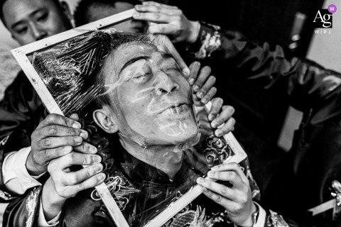 Sichuan artful style wedding detail picture of the bridegroom and his brothers are playing games and The bridegroom needs to penetrate the plastic film with his head showing powerful fingers, which echoes the bridegrooms twisted expression