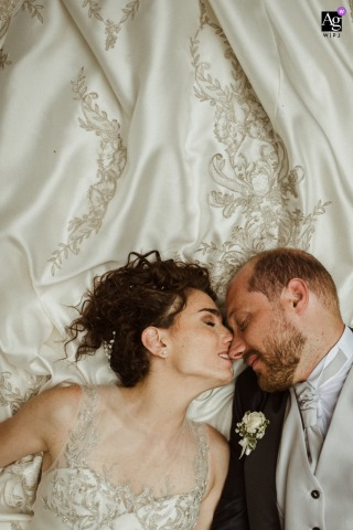 Siena, Tuscany wedding couple artistic image session with a tender nose touch with the brides dress behind them
