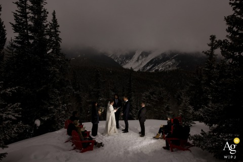 Aspen wedding venue outdoor ceremony photography showing bride and groom reading their vows during their micro wedding at the top of Aspen Mountain in the winter snow