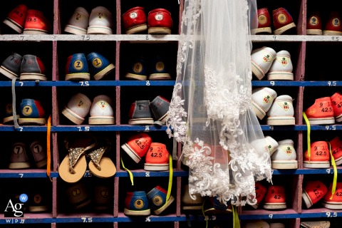 The BackAlley, Butler, PA artful style wedding detail picture showing The brides veil and shoes are displayed amongst the rentable bowling shoes at a wedding venue that also functions as an actual bowling alley