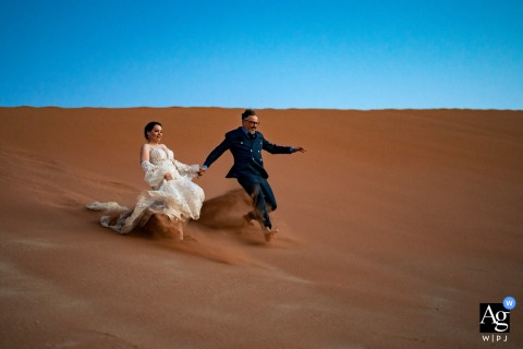 Deadvlei Namibia wedding couple artistic image session resulting in a running Portrait in the desert sand