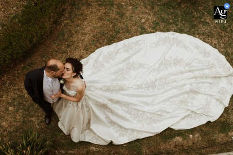 Siena, Tuscany wedding couple artistic image session shot overhead on the lawn with the bride and groom kising
