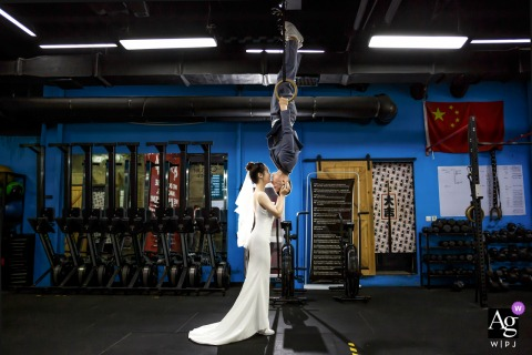 Beijing wedding couple artistic image session at the Physical training hall with an inverted rings kiss