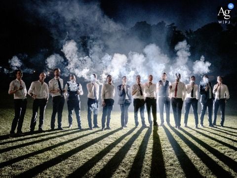 Villa Caroli Zanchi, Italy wedding bridal party artistic image session with the group of the grooms friends made unique by a play of lights that enhances the smoke of the cigars