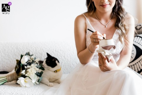 Istanbul artful style wedding detail picture of bride signing shoe as cat is curious about the wedding bouquet