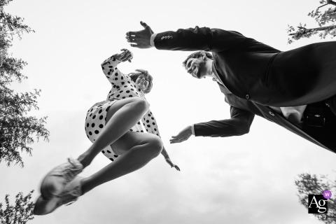 Sesja artystyczna dla pary ślubnej z Galapagar w BW pokazująca Pannę Młodą skaczącą na ramiona stajennych