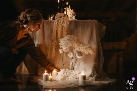 Font-Romeu, Pyrénées-Orientales, Frankreich kunstvolles Hochzeitsdetailbild von einem Empfang in einem Chalet, während die Braut der Tischdekoration den letzten Schliff gibt