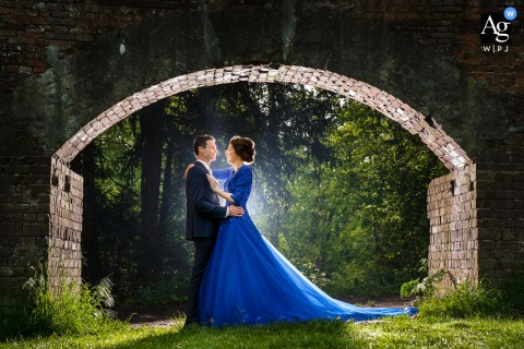 Alblasserdam wedding couple artistic image session in a park as The bride and groom are standing under a bridge and the bride wears a nice blue dress