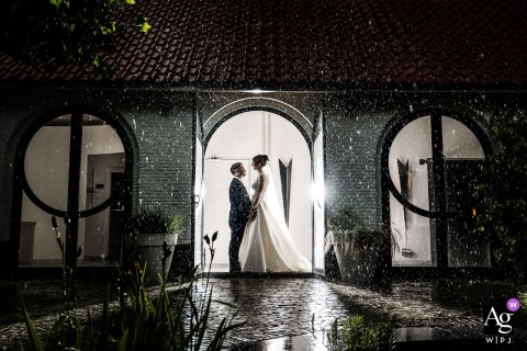 The Mariënhof, Amersfoort wedding couple artistic image session showing The bride and groom are posing inside the rain at the wedding venue