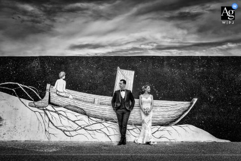 Civitanova Marche wedding couple artistic image session in BW with a boat painting behind the Bride and groom