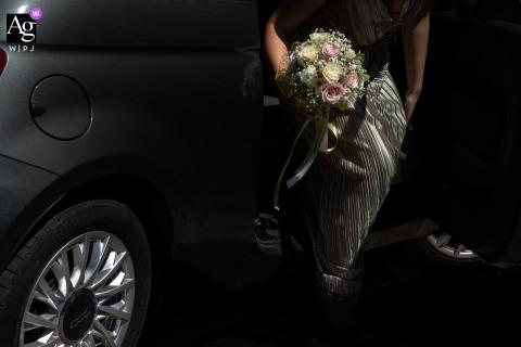 Cerimonia, Gonzaga, Mantoue, Italie photo de détail de mariage de style artistique avec une sous-exposition pour améliorer les détails de la voiture et du bouquet lorsque la mariée arrive
